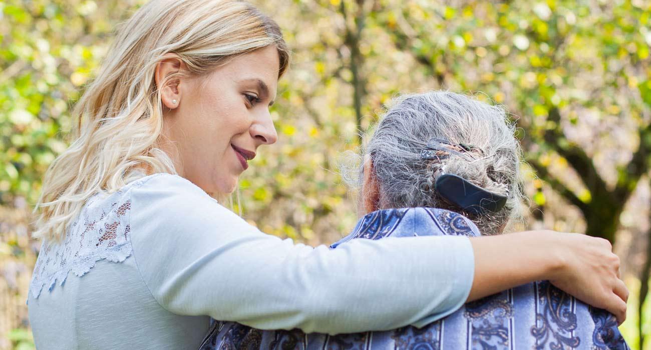Women with arm around elderly woman